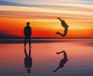 Woman jumping through the air into the water with a beautiful sunset as man watches nearby